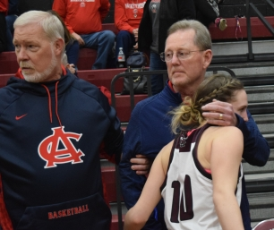 Anderson County assistant coach Bob Osborne embraces Owen County senior Baileigh Young after Saturday's game. Osborne coached at Owen County for 37 years before retiring two years ago. At left is Anderson assistant Jeff Hawkins.
